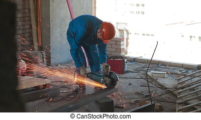 Worker cutting metal beam with grinder