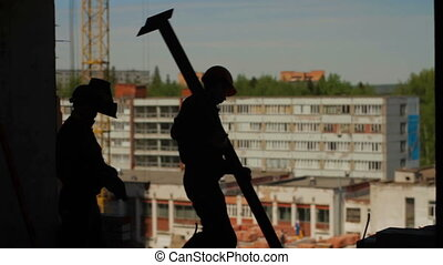 Silhouettes of two workers with metal beam