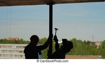 Silhouettes of two builders - Silhouettes of two workers...