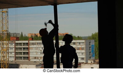 Silhouettes of two workers assemble a metal beam -...