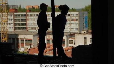 Silhouettes of two workers assemble a beam - Silhouettes of...