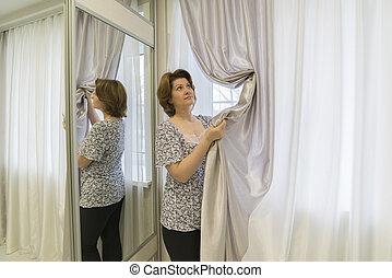 Woman caring for curtains hanging in  window