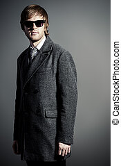 classic suit - Elegant young man in a coat and sunglasses...