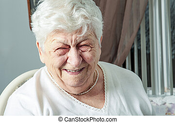 senior woman laughing out loud in living room