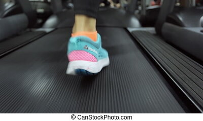 shift movement of the athlete on a treadmill at the gym is very close to the camera, female legs pass forward speed average sneakers light, dark jogging suit