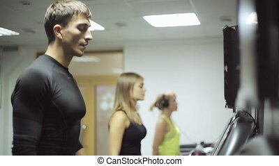 athletes walk on a treadmill uniformly and vigorously, all in tracksuits. regular exercise to warm up muscles before exercise.