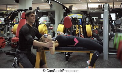 male athlete the coach helps young attractive woman in the gym to engage in the development of the chest muscles, helping to raise the dumbbells and shows how to do it right.