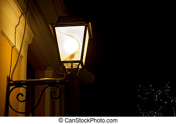 Lit light post - A lit light post holding by a wall on dark...