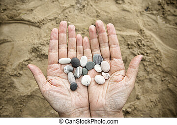 Stonesin female hands on a background of sand. - Stones in...