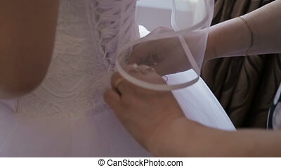bridesmaid tying bow on wedding dress in room bride