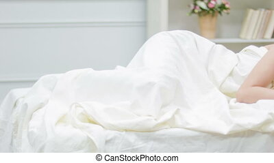 Young depressed woman lies awake in bed