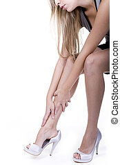 leg shot - woman rubbing her legs over white background