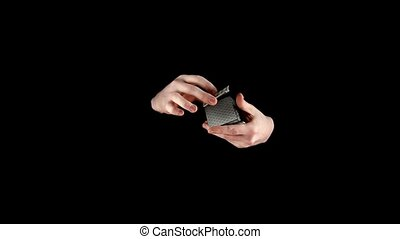 Magician starts showing his trick with cards on black, slow...