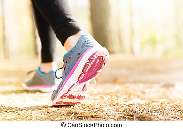 Woman running legs in sunset forest