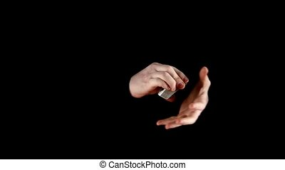 Playing card trick of magicin, on black, slow motion -...