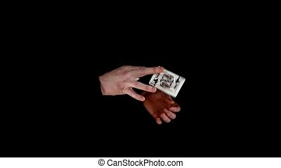 Trick of magician with cards, taking card from nowhere on black, slow motion