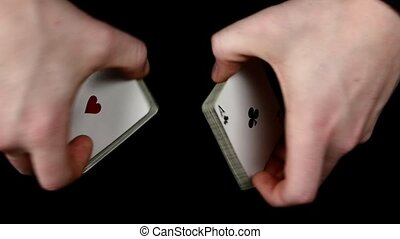 Playing cards being shuffle, on a black surface by magician,...