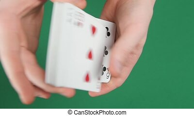 Playing cards being shuffle on a green surface by magician,...