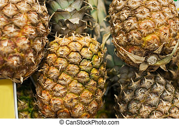 Shelf with pineapples in a supermarket