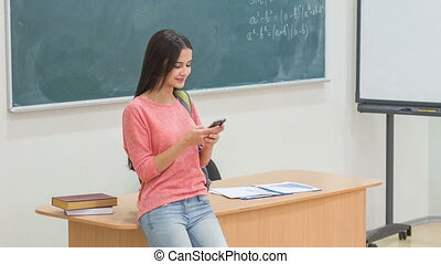 Young female student using her smartphone. - Texting time....