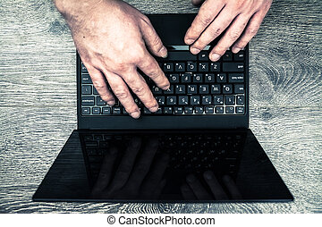 laptop with hands on wood