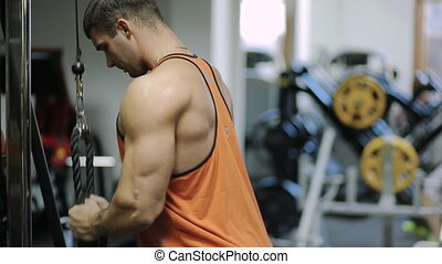 male bodybuilder athlete at the simulator is in a bright shirt, and in the background on the machine shakes his legs lifter weight lifting legs.
