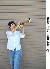 Female trumpet player - Female trumpet player blowing her...