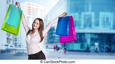 Woman in formal wear with colorful packages on the city...