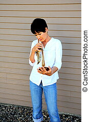 Female trumpet player - Female trumpet player holding her...