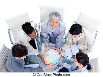 Keen business team holding a terrestrial globe in a meeting...