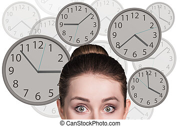 Businesswoman stands among clocks. - Young business woman...