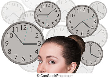 Businesswoman stands among clocks - Young business woman...