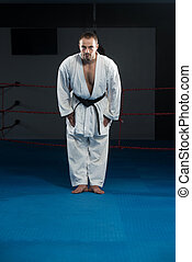 Black Belt Karate Expert With Fight Stance - Young Man...