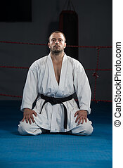 Man In A Kimono With A Black Belt Meditates - Young Man...