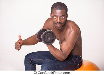 Strong and muscular guy with dumbbell on white background -...