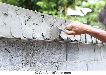 Asian boy hand using trowel with wet concrete wall