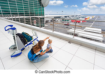 Young mother show to baby boy airplanes in airport - Young...