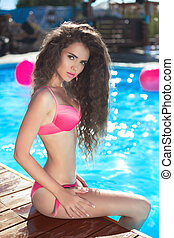 beautiful sexy female bikini model posing in swimming pool,...