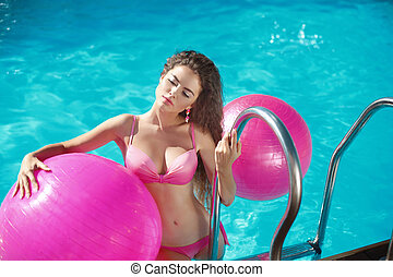 Pilates. Beautiful girl model Relaxing in swimming pool,...
