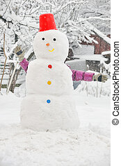 young girl in wintertime making snowman - young girl have...