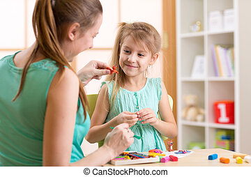 kid girl and mother play colorful clay toys at nursery at home