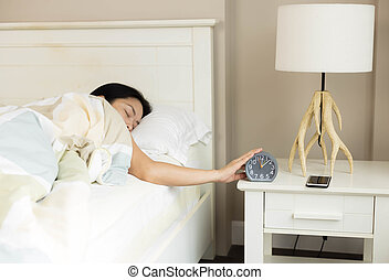 Woman is sleeping with hand stopping alarm clock on the bed