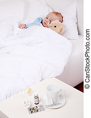Baby is sick - Baby and teddybear lying in bed with cup of...