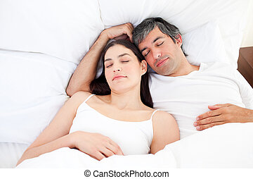 Affectionate couple hugging lying in their bed at home