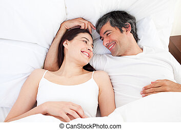 Enamored couple hugging lying in their bed at home