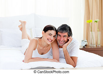 Romantic couple embracing lying on their bed - Portrait of a...
