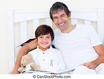Happy father reading with his son sitting on a bed