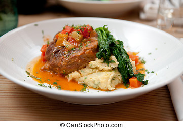 osso buco made with polenta and a tomato sauce with fresh...
