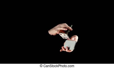 Talanted magician go on showing his trick with cards,...