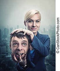 Woman with mans head in her hand - Happy businesswoman with...